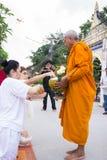 Les gens ont mis des offres de nourriture dans l'aumône de moine bouddhiste roulent pour la substance gluante image stock