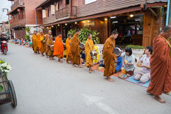 Les gens ont mis des offres de nourriture dans l'aumône de moine bouddhiste roulent pour la substance gluante image libre de droits