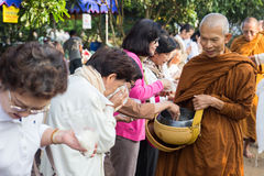 Les gens ont mis des offres de nourriture dans l'aumône de moine bouddhiste roulent pour vir photographie stock libre de droits