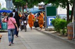 Les gens ont mis des offres de nourriture dans une cuvette bouddhiste d'aumône photos stock