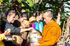 Les gens ont mis la nourriture sur la cuvette d'aumône de moine bouddhiste images libres de droits