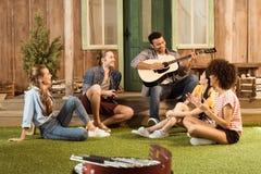 Les gens passant le temps ensemble, homme jouant la guitare tandis que l'autre écoute d'amis Photos stock