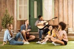 Les gens passant le temps ensemble, homme jouant la guitare tandis que l'autre écoute d'amis Photo libre de droits