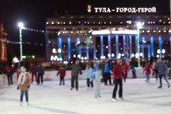 Les gens patinent le soir sur une piste de patinage de ville Texture brouillée photographie stock libre de droits