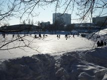 Les gens patinent sur la piste et jouent à l'hockey un jour givré ensoleillé clair photographie stock libre de droits