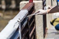 Les gens peignant la barrière avec la couleur blanche Images stock