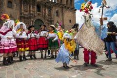 Les gens portant les vêtements traditionnels et les masques dansant le Huaylia pendant le jour de Noël devant la cathédrale de Cu Image libre de droits