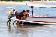 Les gens poussant le bateau avec un auvent à l'océan Voyage autour de Bali image libre de droits