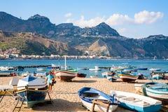 Les gens près des bateaux sur la plage dans la ville de Giardini Naxos Photo stock