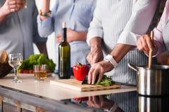 Les gens préparant la nourriture saine dans la cuisine Photos libres de droits