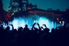 Les gens prenant des photos de fontaine et de lumières avec des smartphones Photos libres de droits