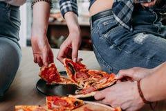 Les gens prenant des tranches de pizza du plat Image libre de droits