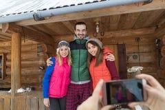Les gens prenant la photo sur la station de vacances en bois de neige d'hiver de Chambre de montagne de pays de groupe futé de té Image libre de droits