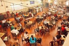 Les gens prenant le petit déjeuner à l'intérieur du café indien traditionnel Images libres de droits