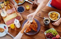Les gens prenant le petit déjeuner à la table avec la nourriture Image libre de droits