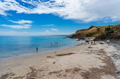 Les gens prenant un bain de soleil et nageant sur la plage le jour ensoleillé Image stock