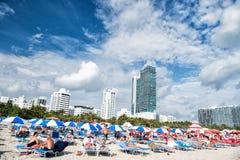 Les gens prenant un bain de soleil sur des chaises de plate-forme sous les parapluies bleus Photo libre de droits