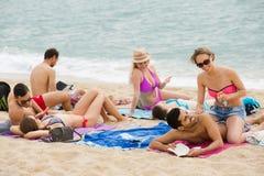 Les gens prenant un bain de soleil sur la plage Image libre de droits