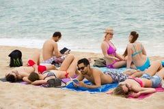 Les gens prenant un bain de soleil sur la plage Photos libres de droits