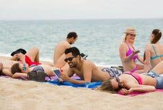 Les gens prenant un bain de soleil sur la plage Photographie stock libre de droits