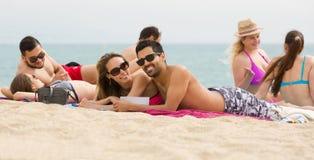 Les gens prenant un bain de soleil sur la plage Images libres de droits