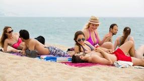 Les gens prenant un bain de soleil sur la plage Photo libre de droits