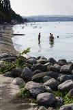 Les gens prenant un bain de soleil sur la plage le 30 juillet 2016 à Desenzano del Garda, Italie Images libres de droits