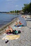 Les gens prenant un bain de soleil sur la plage le 30 juillet 2016 à Desenzano del Garda, Italie Photo stock