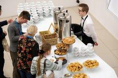 Les gens prennent des petits pains avec des raisins secs sur une pause-café à une conférence Photos libres de droits