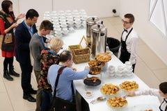 Les gens prennent des petits pains avec des raisins secs sur une pause-café à une conférence Photo stock