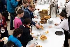 Les gens prennent des petits pains avec des raisins secs sur une pause-café à une conférence Images libres de droits