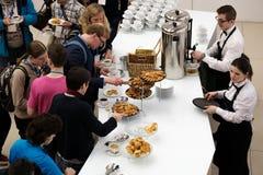 Les gens prennent des petits pains avec des raisins secs sur une pause-café à une conférence Photographie stock