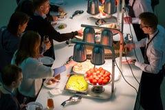 Les gens prennent des petits pains avec des raisins secs sur une pause-café à une conférence Image stock