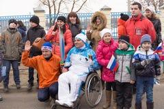 Les gens prennent des photographies du porteur de flambeau dans un fauteuil roulant Photographie stock libre de droits