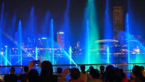 Les gens prennent des photos d'exposition de laser de lumière et d'eau à la plaza d'événement à Singapour banque de vidéos