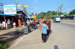 Les gens prient avec le moine et mettent des offres de nourriture dans la cuvette bouddhiste d'aumône photos libres de droits