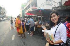 Les gens prient avec le moine et mettent des offres de nourriture dans la cuvette bouddhiste d'aumône photos stock