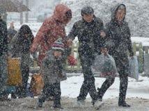 Les gens qui entrent à la maison dans la neige Photographie stock