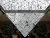 Les gens qui lavent sportif la pyramide inversée du Louvre de l'intérieur à Paris france photographie stock libre de droits