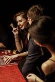 Les gens regardant la belle femme tenant le casino ébrèchent à la table de tisonnier Photographie stock