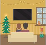 Les gens regardant la TV dans la pièce de deco de Noël Image libre de droits