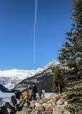 Les gens regardant Lake Louise et montagnes avec le contrail de jet Image libre de droits