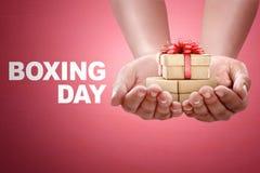 Les gens remettent tenir le boîte-cadeau avec le signe de lendemain de Noël Photo stock