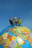 Les gens restant sur le globe Photographie stock libre de droits
