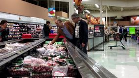 Les gens sélectionnant la viande de épicerie