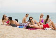 Les gens s'étendant sur le sable à la plage Photos stock