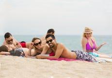 Les gens s'étendant sur le sable à la plage Image libre de droits