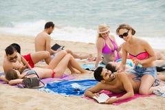 Les gens s'étendant sur le sable à la plage Images stock