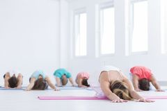 Les gens s'étirant pendant les classes de yoga Image stock