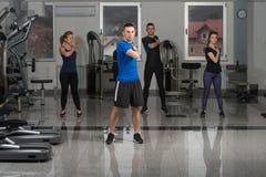 Les gens s'étirant pendant la classe de forme physique au centre de fitness Image libre de droits